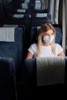 Vrouw die met de trein reist en een medisch masker draagt voor bescherming