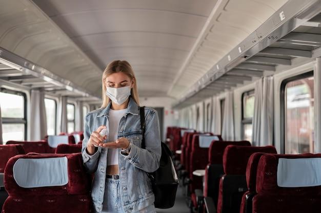 Vrouw die met de trein reist en handdesinfecterende spray gebruikt voor bescherming