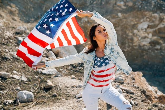 Vrouw die met de vlag van de vs camera bekijkt