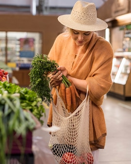 Vrouw die met de zomerhoed producten koopt