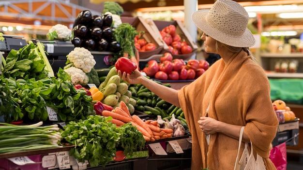 Vrouw die met de zomerhoed zoete paprika koopt