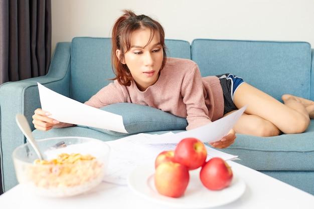 Vrouw die met document thuis werkt