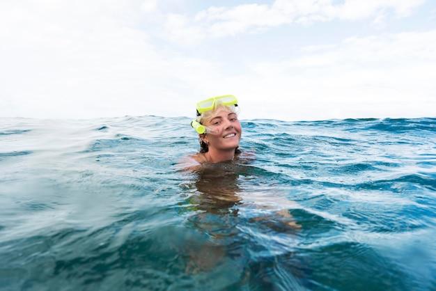Vrouw die met duikuitrusting in de oceaan zwemt