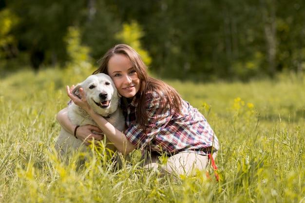 Vrouw die met een hond op het platteland geniet van