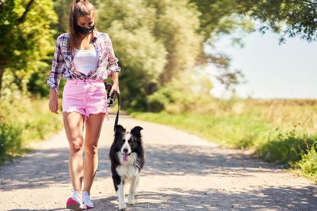 Vrouw die met een hond op het platteland loopt en een masker draagt