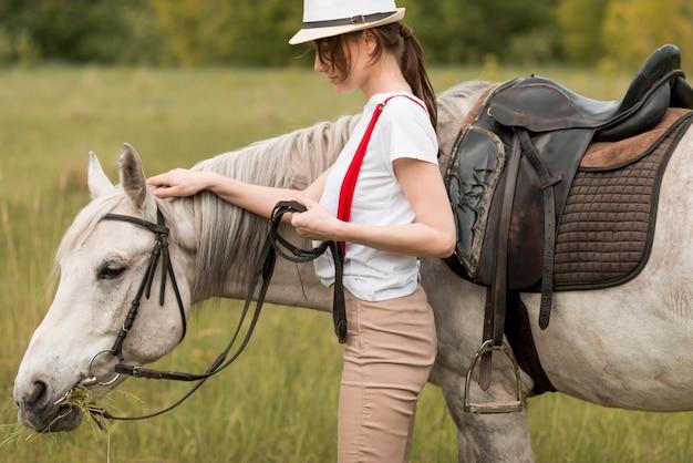 Vrouw die met een paard in het platteland loopt