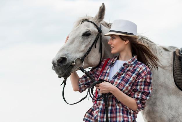 Vrouw die met een paard op het strand loopt
