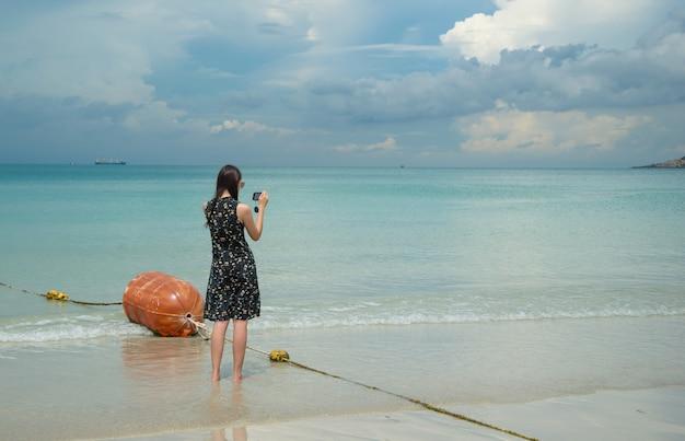 Vrouw die met een smartphone bij het strand van nam sai, chonburi, thailand wordt gefotografeerd