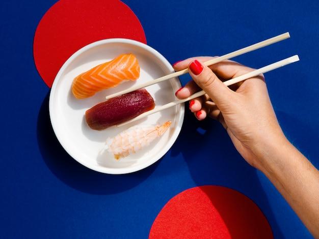 Vrouw die met eetstokjes een tonijnsushi neemt