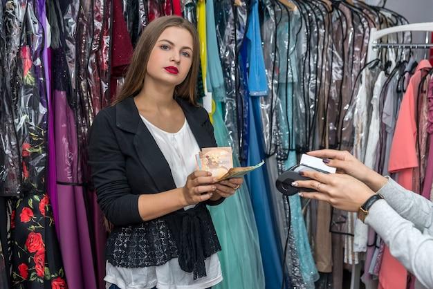 Vrouw die met eurobankbiljetten in winkel betaalt