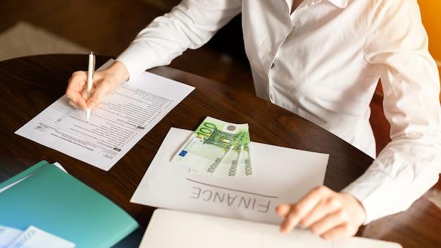 Vrouw die met financiën op de tafel werkt. geld, papieren