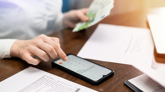 Vrouw die met financiën op de tafel werkt. smartphone, geld, blocnote