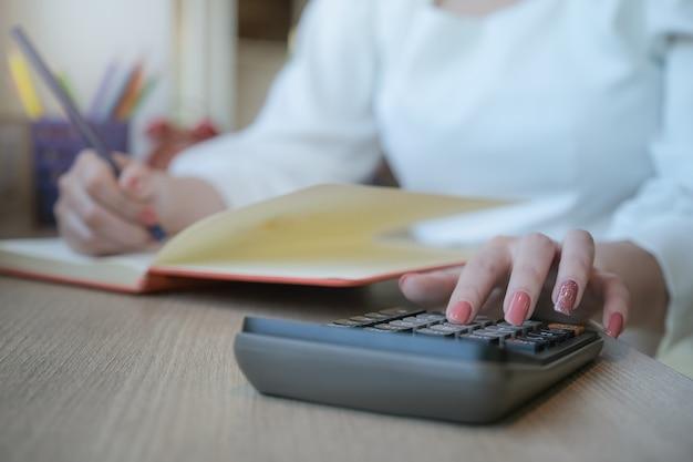 Vrouw die met financiën werkt berekent op calculator en het gebruiken van notitieboekje in bureauruimte.