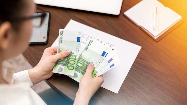 Vrouw die met financiën werkt die geld op de lijst tellen. smertphone, blocnote