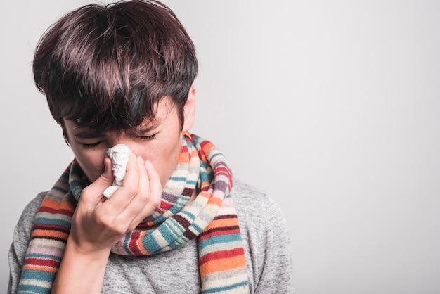 Vrouw die met gesloten ogen haar neus blaast in papieren zakdoekje tegen grijze achtergrond
