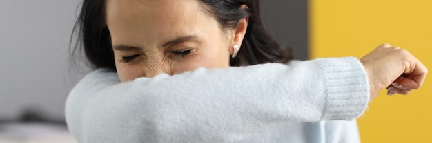 Vrouw die met gesloten ogen thuis in elleboog niest. preventie van infecties bij luchtweginfecties concept