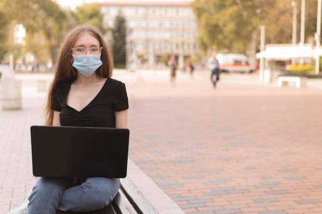 Vrouw die met gezichtsmasker aan laptop buiten werkt
