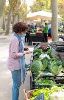 Vrouw die met gezichtsmasker groenten koopt bij een openluchtmarkt. nieuw normaal concept