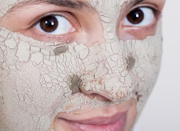 Vrouw die met gezichtsmasker het camera extreme close-up bekijkt