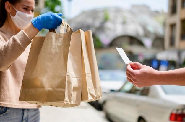 Vrouw die met gezichtsmasker het winkelen zakken ontvangt