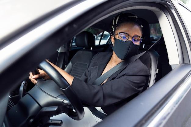 Vrouw die met gezichtsmasker in de achterspiegel kijkt om auto om te keren