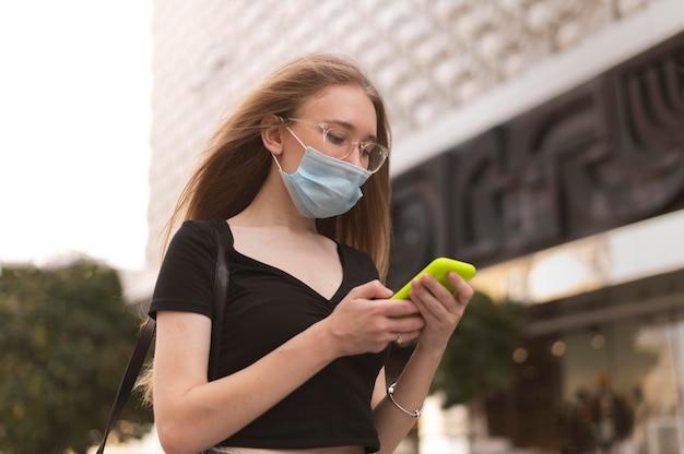 Vrouw die met gezichtsmasker in de stad loopt terwijl zij haar telefoon controleert