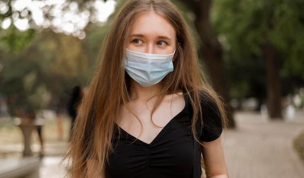Vrouw die met gezichtsmasker in het park loopt