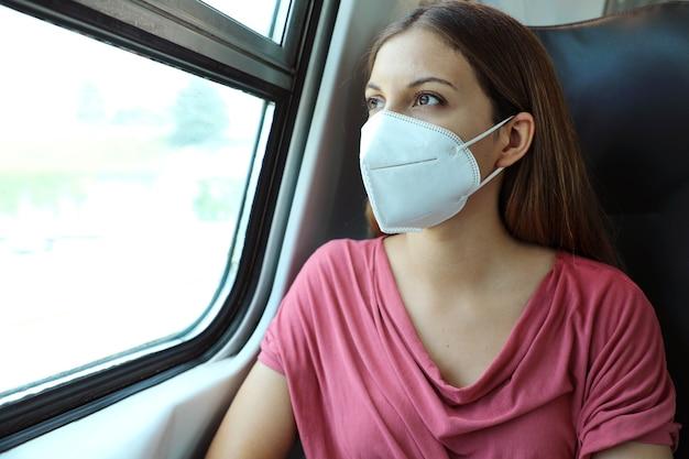 Vrouw die met gezichtsmasker kn95 ffp2 door treinraam kijkt