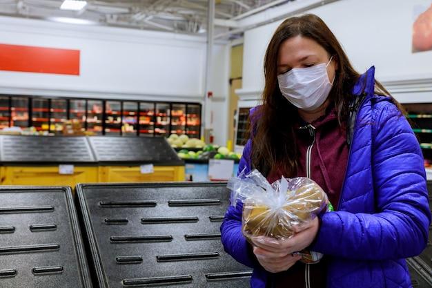 Vrouw die met gezichtsmasker laatste zak aardappel houdt bij opslag met lege planken.