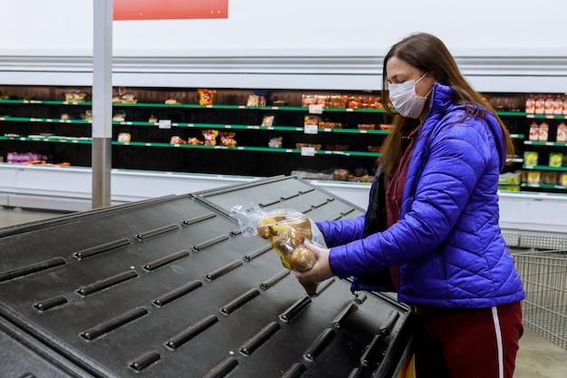 Vrouw die met gezichtsmasker laatste zak aardappel houdt bij supermarkt met lege planken.