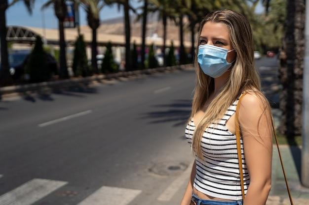 Vrouw die met gezichtsmasker rond de stad lopen tijdens de pandemie van het coronavirus