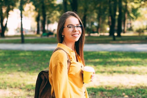 Vrouw die met glazen een kop warme drank in park houdt