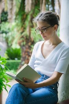 Vrouw die met glazen geschiedenisboeken lezen