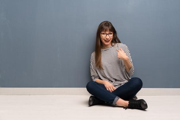 Vrouw die met glazen op de vloer met verrassingsgelaatsuitdrukking zit