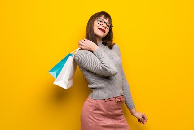 Vrouw die met glazen over gele muur heel wat het winkelen zakken houdt