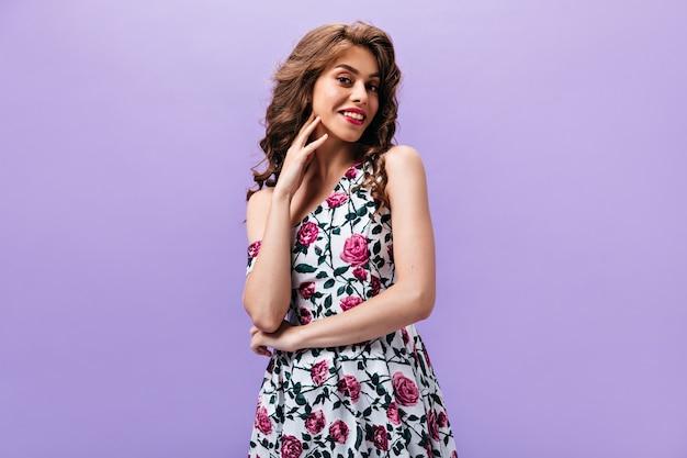 Vrouw die met golvend haar camera onderzoekt. prachtig meisje met heldere lippen in stijlvolle zomerjurk poseren op geïsoleerde achtergrond.