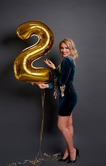 Vrouw die met gouden ballon het cijfer bouwt