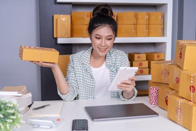 Vrouw die met haar digitaal tablet en de doos van het koerierspakket thuis kantoor werken
