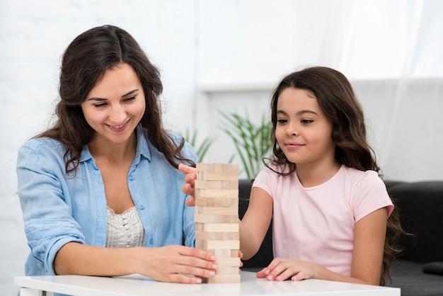 Vrouw die met haar dochter een internaatsspel speelt
