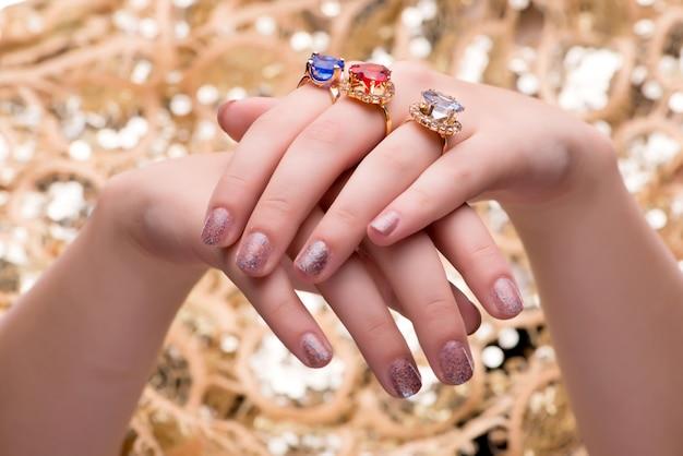Vrouw die met haar juwelenringen in manierconcept pronken