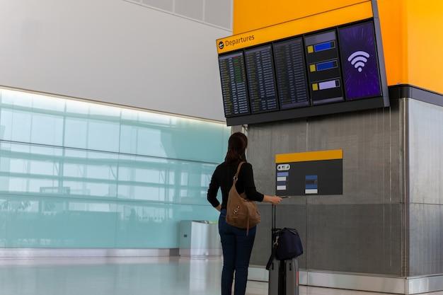 Vrouw die met handbagage de vluchtinformatie in de luchthaven bekijkt.