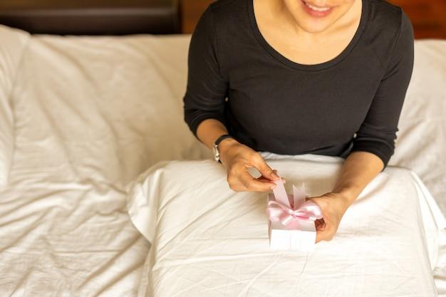 Vrouw die met handen glimlachen die valentijnskaart openen stellen in slaapkamer voor.