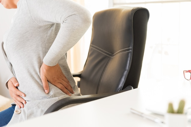 Vrouw die met handen haar rugpijn houdt. office-syndroom en gezondheidszorgconcept.