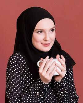 Vrouw die met headcover weg koffiekop over donkere oppervlakte houdt kijkt