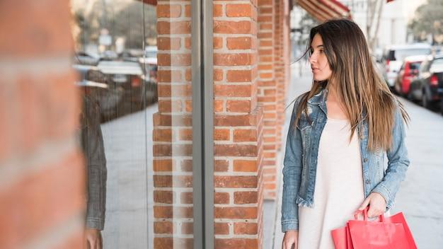 Vrouw die met het winkelen pakketten winkelvensters bekijkt