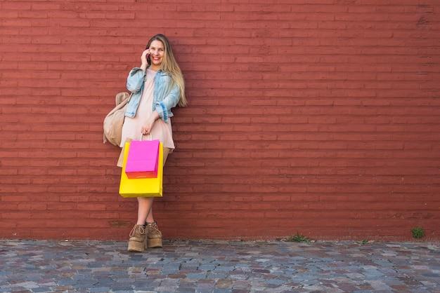 Vrouw die met het winkelen zakken telefonisch bij muur spreekt