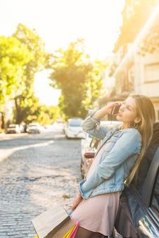 Vrouw die met het winkelen zakken telefonisch in straat spreekt