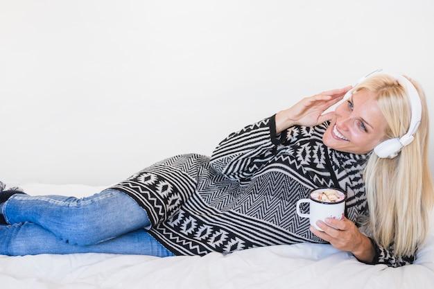 Vrouw die met hete drank van muziek op bed geniet