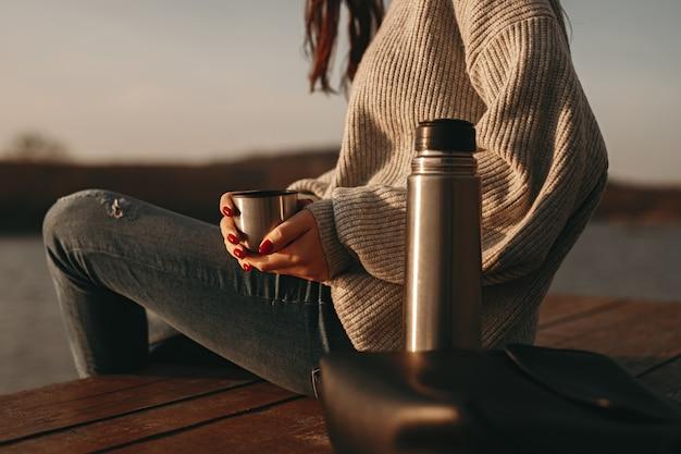 Vrouw die met hete koffie dichtbij meer rust