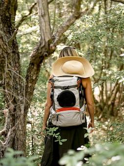 Vrouw die met hoed bos onderzoekt